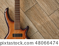 Power of musical instrument. Top view of the brown electric guitar lying on the wooden floor. 48066474