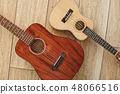 Perfect sound. Top view of the acoustic and ukulele guitars lying close to each other on the wooden 48066516