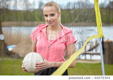 Sports games and people concept. Young woman in sportswear volle 48078364