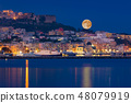 Full moon rises over coast of seaside city 48079919