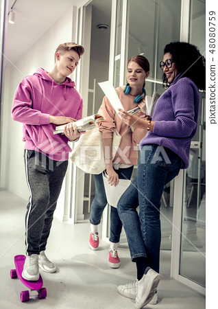 Blonde student standing on his skate talking to his friends 48080759