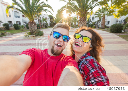Travel, vacation and holiday concept - Funny couple in sunglasses having fun and taking selfie 48087058