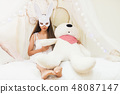 brunette woman with rabbit mask hold big bear 48087147