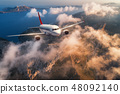 Airplane is flying over mountains and low clouds  48092140