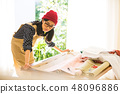 A woman sewing 48096886