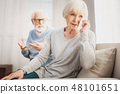 Aged woman having tears while listening to her angry husband 48101651