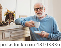 Respectful elderly man drinking tea standing near fireplace 48103836