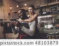 Beautiful girl barista hugs a man holding a tablet 48103879