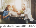 A company of friends sits in a cafe at the table 48104027