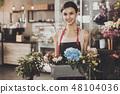 Portrait of beautiful girl florist in flower shop 48104036