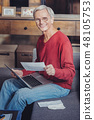 Emotional pensioner using modern technologies and looking happy 48105753