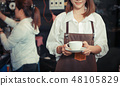 Female barista serving coffee to customer in cafe. 48105829