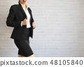 Pretty girl in black suit standing and smiling. 48105840