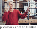 Clever aged man looking at the important document while talking on the phone 48106841