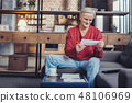 Cheerful pensioner smiling while looking at the bills in his hands 48106969
