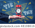 Man's hand facing up holding dynamite bundle with time bomb on blackboard background with chalk 48108616
