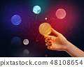 Female hand holding neon Saturn model between fingers with colorful neon planets and outer space on 48108654