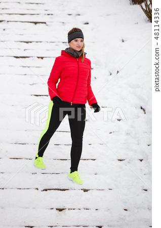 Woman wearing sportswear exercising during winter 48114336