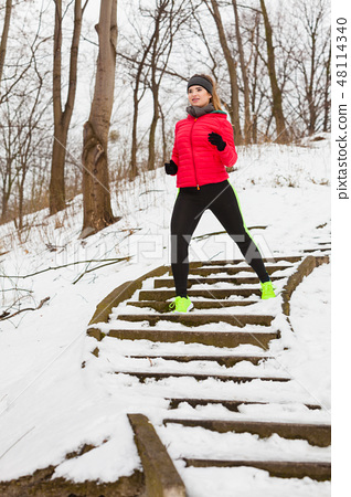 Woman wearing sportswear exercising outside during winter 48114340