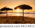 Two beach umbrellas at sunrise on a sandy beach. Tropical island. 48114811