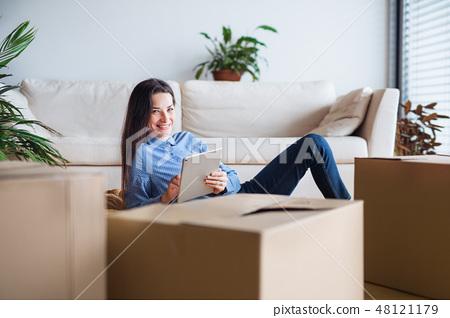 A young woman with tablet and cardboard boxes moving in a new home. 48121179