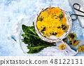 Dandelion flowers in wicker bowl top view 48122131