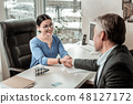 Dark-haired beautiful asian woman in a blue shirt shaking hands with a new employee 48127172