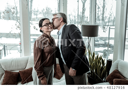 Tall grey-haired handsome man in a blue shirt kissing a woman on a cheek 48127916
