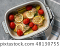 Oven baked salmon with leek and tomatoes. 48130755