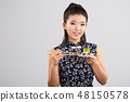 Sushi woman holding sushi with chopsticks 48150578