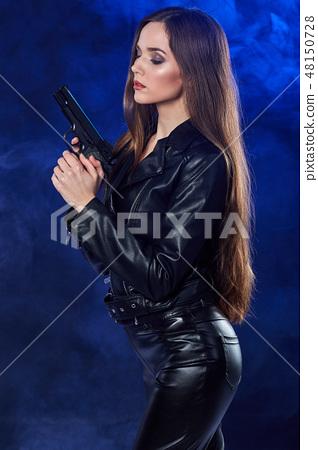 beautiful sexy girl holding gun . smoke background 48150728