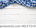Blue checkered kitchen tablecloth on wooden table. 48157310