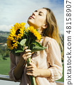 Happy beautiful young woman holding sunflowers 48158907