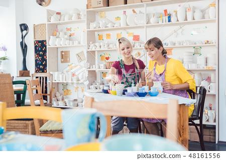 Women friends looking at lots of self-made tableware in workshop 48161556