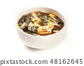 A photo of a bowl of miso soup with tofu, scallions, noodles, wakame, and enoki mushrooms, on a 48162645