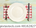 An overhead photo of a white plate with a fork and a knife on a teal background with copy space 48162827