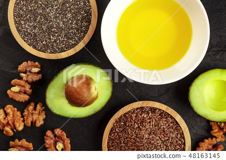 An overhead photo of the ingredients of a healthy vegan omega 3 diet. Avocado, nuts, chia and flax 48163145