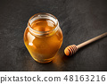 A photo of a honey dipper and jar on a black background with a place for text. Selective focus 48163216