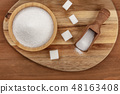 An overhead photo of a bowl and a scoop of white sugar, with sugar cubes, shot from the top on dark 48163408