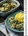 Chicken breast baked with spinach cream sauce . 48163996