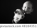 Cute young girl and her wire fox terrier puppy in the studio in monochrome 48164351