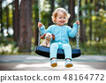 Adorable toddler girl with soft toy dog having fun on a swing on summer day 48164772