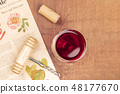 An overhead photo of a glass of red wine with a vintage corkscrew and a cork, shot on a blurred 48177670