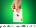 A hand holding an ace of hearts against a green background with copyspace 48177814