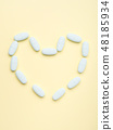 Blue pills forming heart shape on pastel yellow 48185934