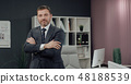 Businessman standing, office interior on background, man in suit. 48188539