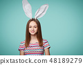 Girl wearing bunny ears holding a banner 48189279
