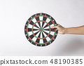 Hand holding target dart board on gray background. 48190385