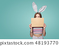 Girl wearing bunny ears holding a blank letter envelope 48193770
