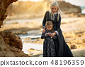 Woman and bonding with little daughter in classic dress standing on the coast 48196359